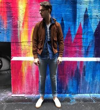 Come indossare e abbinare: giubbotto bomber in pelle scamosciata marrone, camicia a maniche lunghe in chambray blu scuro, t-shirt girocollo a righe orizzontali bianca e blu scuro, jeans aderenti azzurri