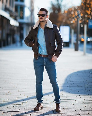 Come indossare e abbinare: giubbotto bomber in pelle marrone scuro, camicia di jeans azzurra, jeans aderenti blu, stivali casual in pelle marroni