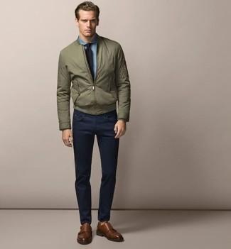 Come indossare e abbinare: giubbotto bomber verde oliva, camicia elegante in chambray azzurra, chino blu scuro, scarpe double monk in pelle marroni