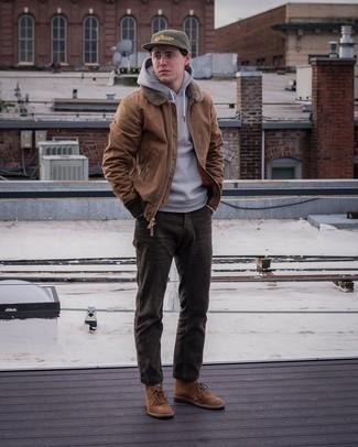 Come indossare e abbinare una felpa con cappuccio grigia: Per un outfit quotidiano pieno di carattere e personalità, potresti indossare una felpa con cappuccio grigia e jeans di velluto a coste marrone scuro. Scegli un paio di chukka in pelle scamosciata marroni per un tocco virile.