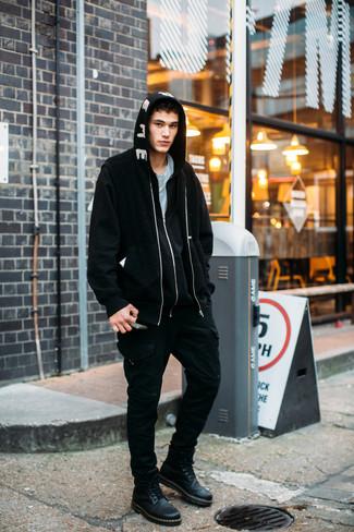 Come indossare e abbinare: giubbotto bomber di pile nero, felpa con cappuccio stampata nera e bianca, t-shirt girocollo azzurra, pantaloni cargo neri