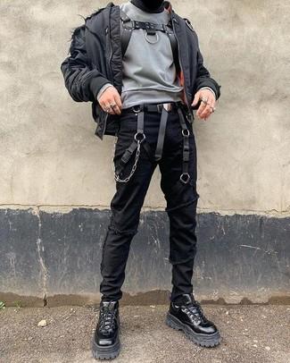 Come indossare e abbinare: giubbotto bomber nero, felpa grigia, jeans aderenti strappati neri, stivali da lavoro in pelle neri