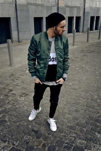 Moda uomo anni 20: Prova ad abbinare un giubbotto bomber verde scuro con jeans strappati neri per un outfit rilassato ma alla moda. Scegli uno stile classico per le calzature e indossa un paio di sneakers basse in pelle bianche.