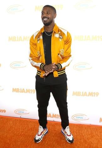 Come indossare e abbinare: giubbotto bomber di raso giallo, t-shirt girocollo nera, pantaloni sportivi neri, scarpe sportive multicolori