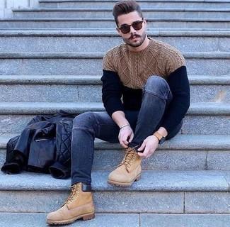 Come indossare e abbinare: giubbotto bomber in pelle trapuntato nero, maglione a trecce blu scuro, jeans aderenti blu scuro, stivali da lavoro in pelle scamosciata marrone chiaro