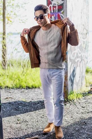 Come indossare e abbinare: giubbotto bomber in pelle scamosciata terracotta, maglione a trecce beige, jeans bianchi, stivali chelsea in pelle scamosciata marrone chiaro