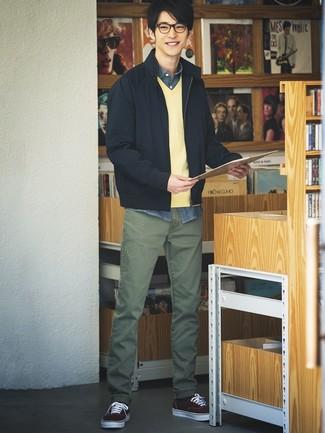 Come indossare e abbinare: giubbotto bomber blu scuro, maglione con scollo a v giallo, camicia a maniche lunghe in chambray blu scuro, chino verde oliva