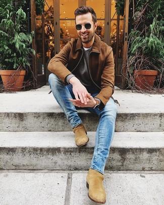 Come indossare e abbinare: giubbotto bomber in pelle scamosciata marrone, maglione con scollo a v grigio, t-shirt girocollo bianca, jeans aderenti blu