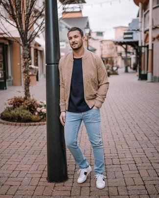 Come indossare e abbinare: giubbotto bomber in pelle scamosciata marrone chiaro, maglione girocollo blu scuro, jeans azzurri, sneakers basse bianche