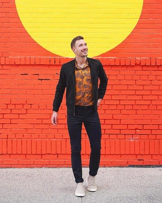 Come indossare: giubbotto bomber in pelle scamosciata nero, camicia a maniche lunghe stampata arancione, jeans neri, stivali chelsea in pelle scamosciata grigi