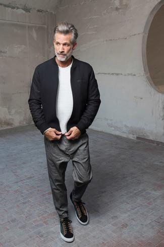 Come indossare e abbinare: giubbotto bomber di lana nero, maglione girocollo bianco, chino grigi, sneakers basse in pelle scamosciata verde scuro