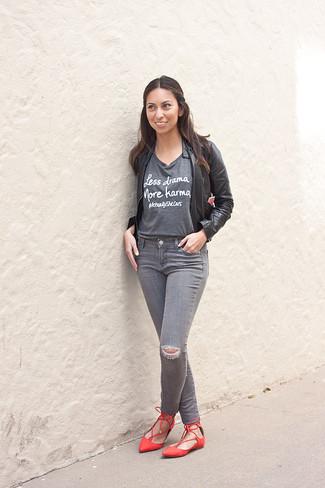 Come indossare: giubbotto bomber in pelle nero, t-shirt girocollo stampata grigia, jeans aderenti strappati grigi, ballerine in pelle rosse