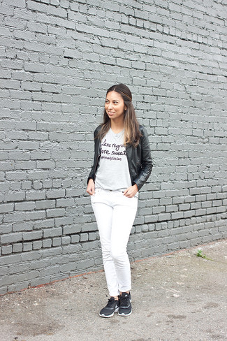 Come indossare: giubbotto bomber in pelle nero, t-shirt girocollo stampata grigia, jeans bianchi, scarpe sportive nere