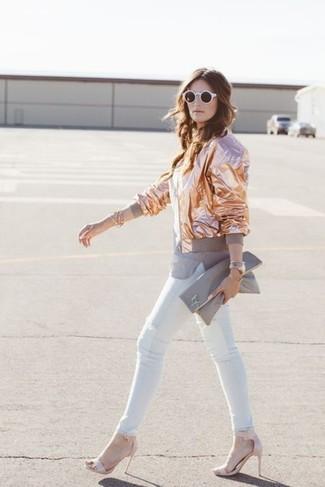Come indossare e abbinare: giubbotto bomber dorato, t-shirt girocollo grigia, jeans aderenti bianchi, sandali con tacco in pelle rosa