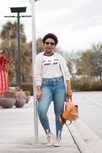 Come indossare e abbinare: giubbotto bomber di pile bianco, t-shirt girocollo stampata bianca e blu, jeans aderenti azzurri, sneakers basse in pelle bianche