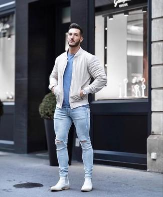 Come indossare: giubbotto bomber beige, t-shirt girocollo blu, jeans aderenti strappati azzurri, stivali chelsea in pelle scamosciata bianchi