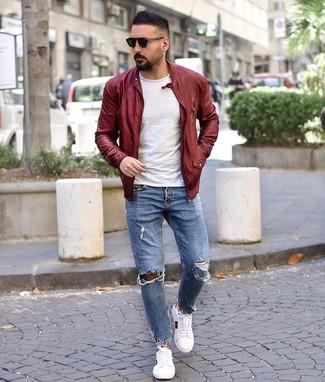 Come indossare e abbinare: giubbotto bomber in pelle bordeaux, t-shirt girocollo bianca, jeans strappati azzurri, sneakers basse stampate bianche