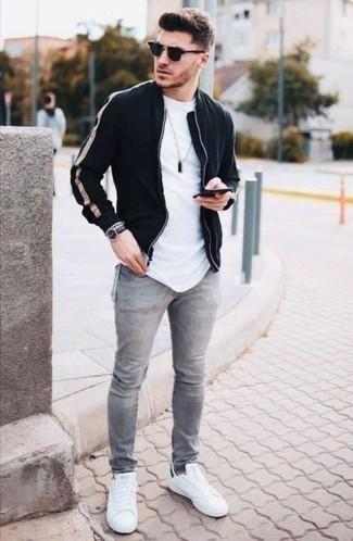 Come indossare e abbinare jeans grigi: Per un outfit quotidiano pieno di carattere e personalità, scegli un outfit composto da un giubbotto bomber nero e jeans grigi. Rifinisci questo look con un paio di sneakers basse di tela bianche e verdi.