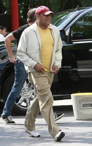 Come indossare e abbinare: giubbotto bomber bianco, t-shirt girocollo gialla, pantaloni cargo beige, scarpe sportive bianche