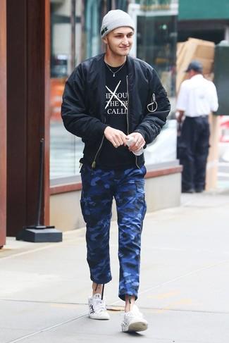 Come indossare e abbinare: giubbotto bomber nero, t-shirt girocollo stampata nera e bianca, pantaloni cargo mimetici blu, sneakers basse in pelle stampate bianche