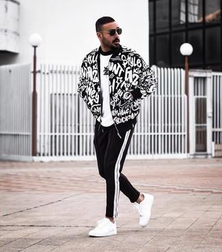 Come indossare e abbinare: giubbotto bomber stampato nero e bianco, t-shirt girocollo stampata bianca e nera, pantaloni sportivi neri e bianchi, sneakers basse in pelle bianche