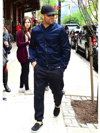Come indossare e abbinare: giubbotto bomber blu scuro, t-shirt girocollo bianca, pantaloni sportivi neri, sneakers senza lacci di tela nere