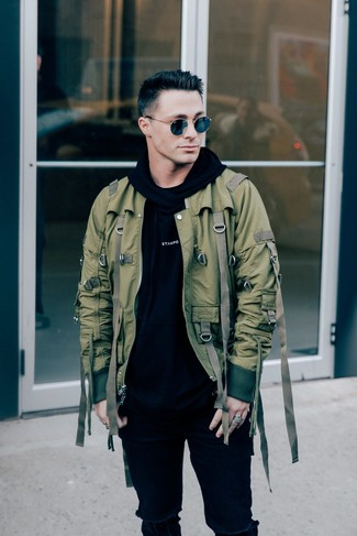 Come indossare e abbinare: giubbotto bomber verde oliva, felpa con cappuccio stampata nera e bianca, jeans aderenti strappati neri, occhiali da sole neri