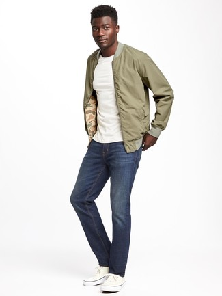 Come indossare e abbinare scarpe da ginnastica di tela bianche: Vestiti con un giubbotto bomber verde oliva e jeans blu scuro per un look trendy e alla mano. Scarpe da ginnastica di tela bianche sono una splendida scelta per completare il look.