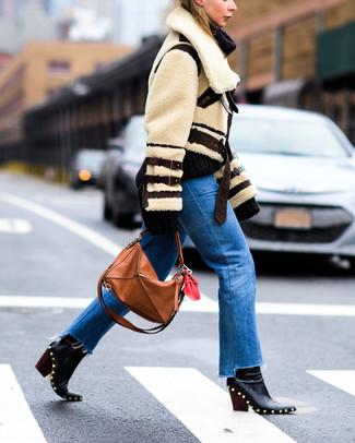 Scegli un giubbotto di shearling beige e jeans blu per creare un look raffinato e glamour. Rifinisci il completo con un paio di stivaletti in pelle con borchie neri di Alexander McQueen.