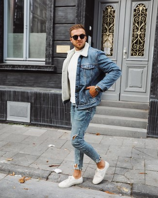 Come indossare e abbinare: giubbotto in shearling di jeans blu, maglione a trecce bianco, jeans aderenti strappati azzurri, sneakers basse bianche