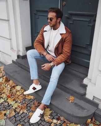 Come indossare e abbinare: giubbotto in shearling terracotta, maglione a trecce bianco, jeans azzurri, sneakers basse in pelle stampate bianche
