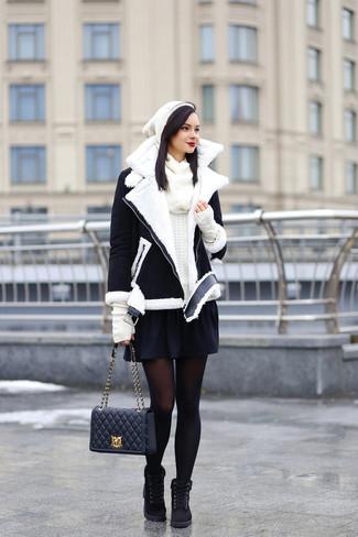 Come indossare: giubbotto in shearling nero e bianco, maglione girocollo bianco, gonna a pieghe nera, stivali piatti stringati in pelle scamosciata neri