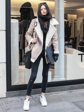 Come indossare e abbinare: giubbotto in shearling beige, maglione girocollo nero, jeans aderenti neri, sneakers basse in pelle bianche