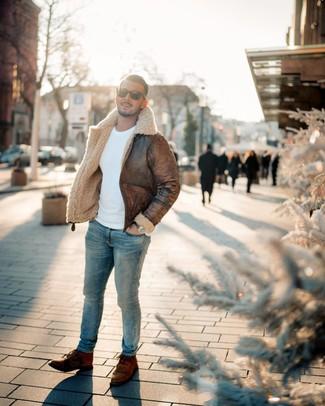 Come indossare e abbinare: giubbotto in shearling marrone, maglione girocollo bianco, jeans aderenti azzurri, stivali casual in pelle marroni