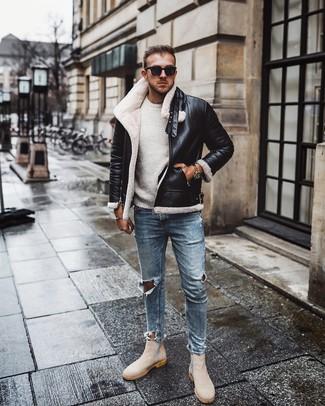 Come indossare e abbinare: giubbotto in shearling nero e bianco, maglione girocollo bianco, jeans aderenti strappati azzurri, stivali chelsea in pelle scamosciata beige