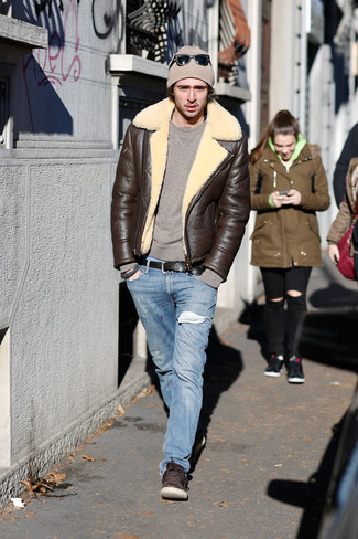 Come indossare e abbinare: giubbotto in shearling marrone scuro, maglione girocollo marrone, jeans azzurri, sneakers basse in pelle marrone scuro