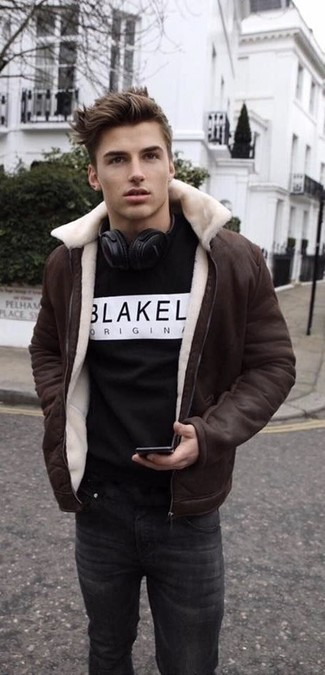 Come indossare: giubbotto in shearling marrone scuro, felpa stampata nera e bianca, jeans neri