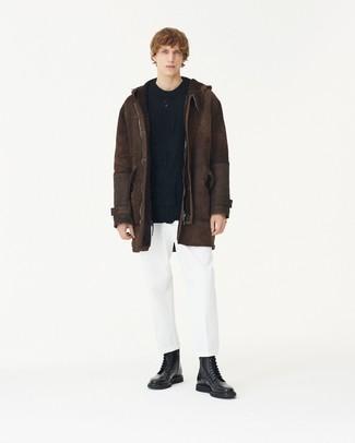 Come indossare: giubbotto in shearling marrone scuro, maglione a trecce nero, chino bianchi, stivali casual in pelle neri