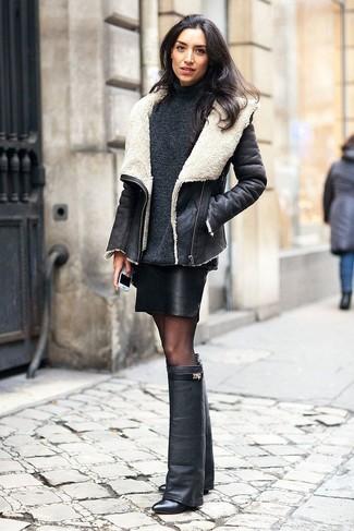 Questo abbinamento di un giubbotto di shearling nero e bianco e una minigonna in pelle nera attira l'attenzione per le ragioni giuste. Stivali al ginocchio in pelle neri sono una buona scelta per completare il look.