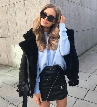Come indossare: giubbotto in shearling nero, maglione oversize azzurro, minigonna in pelle nera, occhiali da sole neri