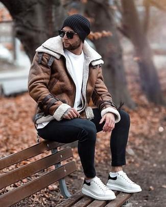 Come indossare e abbinare jeans aderenti neri: Abbina un giubbotto in shearling marrone con jeans aderenti neri per vestirti casual. Sneakers basse in pelle bianche e nere sono una buona scelta per completare il look.