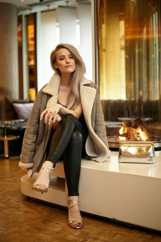 Come indossare: giubbotto in shearling marrone, t-shirt girocollo marrone scuro, pantaloni skinny in pelle neri, sandali con tacco in pelle dorati