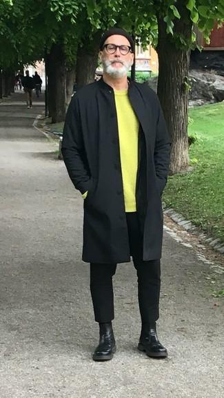 Come indossare e abbinare: impermeabile nero, maglione girocollo lime, chino neri, stivali chelsea in pelle neri