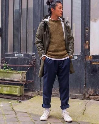 Come indossare e abbinare: impermeabile verde oliva, maglione girocollo marrone, t-shirt girocollo bianca, pantaloni sportivi blu scuro