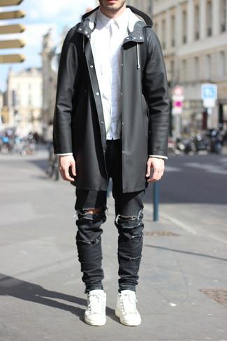 Come indossare e abbinare: impermeabile nero, camicia elegante bianca, jeans aderenti strappati neri, sneakers basse in pelle bianche