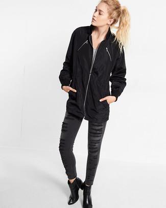 Come indossare: impermeabile nero, t-shirt con scollo a v a righe orizzontali bianca e nera, jeans aderenti strappati grigio scuro, stivaletti in pelle neri