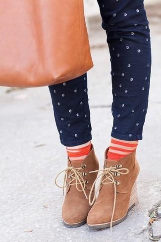 Come indossare e abbinare: jeans aderenti a pois blu scuro, stivaletti con zeppa in pelle scamosciata marrone chiaro, borsa shopping in pelle terracotta, calzini a righe orizzontali arancioni