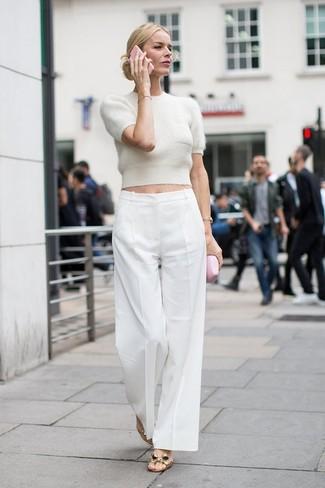 Come indossare: maglione a maniche corte beige, pantaloni larghi bianchi, sandali piatti in pelle dorati, orologio dorato
