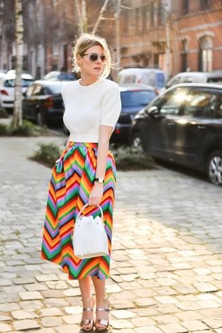 Come indossare e abbinare: maglione a maniche corte bianco, gonna longuette con motivo a zigzag multicolore, sandali con tacco in pelle dorati, borsa a secchiello in pelle bianca