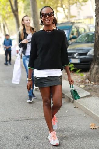 Come indossare: maglione a maniche corte nero, t-shirt girocollo bianca, minigonna in pelle nera, scarpe sportive arancioni